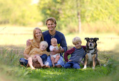 Exterior relajante de la familia joven feliz con el perro casero Fotografía de archivo libre de regalías