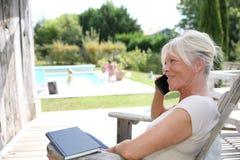 Exterior relajante de la mujer mayor por la piscina Imagen de archivo