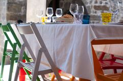 Exterior of a restaurant with a laid out table ready for lunch, with colorful chairs of red, white and natural wood color royalty free stock photos