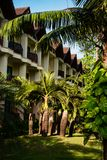 Tropical resort hotel building in green foliage. Exterior shot of contemporary building with hotel rooms and green meadow with plants stock photography