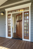 Exterior shot of an open Wooden Front Door. Vertical shot of wooden front door of an upscale home with windows Royalty Free Stock Image