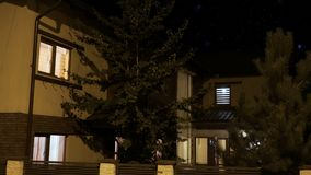 Exterior of a smart house illuminated gradually in every room in a residential neighborhood at night -. Exterior of a smart house illuminated gradually in every