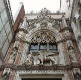 Exterior of St Marks Basilica, Venice. Exterior of St Marks Basilica in Venice, Italy showing colored marble, stone carving, arched windows and door lintel Stock Images