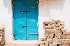 Exterior velho da casa, porta azul e tijolos empilhados em Madurai, Índia imagem de stock