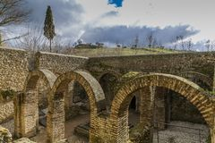 Exterior view of the Arab baths with its walls, arches and stone floor in the city of Ronda. Wonderful day with abundant gray clouds in the province of Malaga stock image