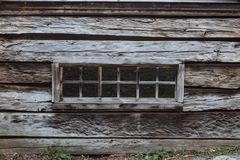 Exterior view of a bank of windows in an old mountain log cabin. Horizontal aspect Stock Image