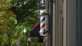 Exterior View of Barber Pole. 9199 A daytime exterior view of a spinning barber pole outside an establishment in a small town stock video