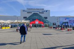 Exterior view of Excel Exhibition Centre, London. London, UK - February 16, 2018: Rear view of man walking towards the entrace of Excel Exhibition Centre at royalty free stock photo