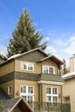 Exterior view of a house with balcony and snow covered roof in winter. The towering coniferous tree behind the home can be seen against cloudy blue sky stock images