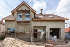 Exterior view of new house under construction and painting. External plaster of the walls of a two-story house. Exterior view of new house under construction Royalty Free Stock Photos