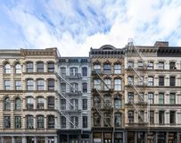 Exterior view of old apartment buildings in the SoHo neighborhood of Manhattan in New York City with empty blue sky. Background overhead stock photo
