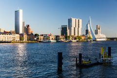 Exterior view of the promenade at the Boompjeskade Street with a. ROTTERDAM, NETHERLANDS - MAY 25, 2017: Exterior view of the Erasmus Bridge at sunset and the Stock Image