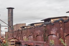 Exterior view of a warehouse district, old brick architecture, smokestack, rusting metal structures. Horizontal aspect stock photography