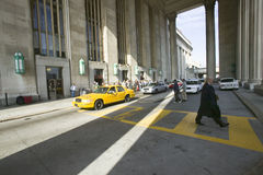 Exterior view of yellow taxi cab and walking business man in front of the 30th Street Station, a national Register of Historic Pl. Aces, AMTRAK Train Station in stock photography
