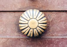 Exterior vintage door handle with a bronze finish on a brown front door in historic building Catania, Sicily, Southern Italy.  royalty free stock images