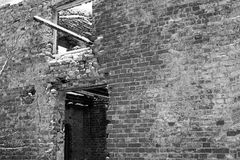 Exterior wall of an abandoned ruined brick house with a window and a doorway in winter, black and white photo. Exterior wall of an abandoned ruined brick house Stock Image