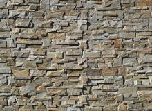 Exterior wall cladding made of   natural stones with irregular shapes. Colors are shades of gray and brown.  royalty free stock photos