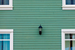 Exterior wall green siding center lamp and windows Royalty Free Stock Photo