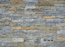 Exterior wall made of different shapes natural stone bricks, with colors brown and gray. Background and texture. stock photography