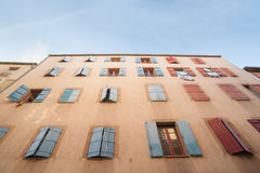 Exterior wall with many windows and shutters, building and archi Stock Photos
