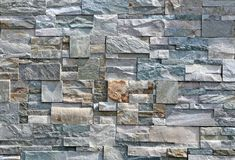 Exterior wall stone cladding made of rocks with different shapes and colors. stock photography