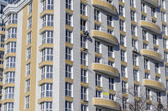 Exterior wall white building with yellow balconies close-up. Exterior wall white building with yellow balconies and working man Royalty Free Stock Photography