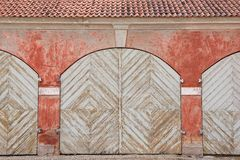 Exterior of the weathered white painted wooden gates and the red wall. Stock Images