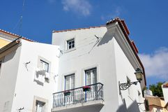 House in Lisboa, Portugal. Exterior of white house with balcony in Lisboa, Portugal against blue skies on sunny day royalty free stock photography