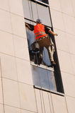 Exterior window washing. Window washer washing high office building windows hanging outside the building on ropes Royalty Free Stock Image