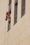 Exterior window washing. Window washer washing high office building windows hanging outside the building on ropes Stock Photos