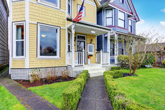 Exterior of yellow family house with American flag. Concrete walkway lead to small covered porch. Northwest, USA Stock Photography