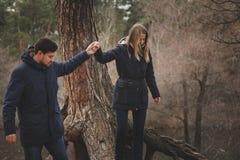 Exteriores felizes dos pares novos loving junto em acolhedor aquecem a caminhada na floresta do outono Imagens de Stock