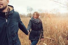 Exteriores felizes dos pares novos loving junto em acolhedor aquecem a caminhada na floresta do outono Fotos de Stock Royalty Free