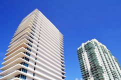 Exteriors of  luxury condominium towers in Miami Beach,Florida. Exteriors of two luxury condominium towers soaring high above street level in Miami Beach,Florida royalty free stock photography