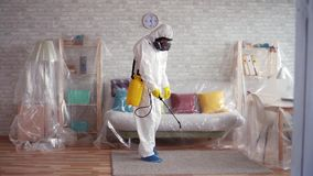 Exterminator cleans the carpet with a spray