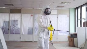 Exterminator in overalls and a protective mask sprays pesticide with a sprayer