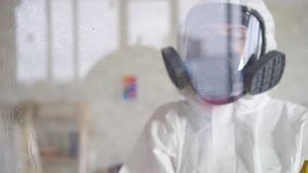 Exterminator in protective clothing and a protective carries out the surface treatment
