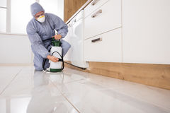 Exterminator Spraying Pesticide In Kitchen. Exterminator In Workwear Spraying Pesticide With Sprayer Royalty Free Stock Photography