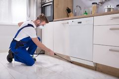 Exterminator Worker Spraying Insecticide Chemical. Young Male Exterminator Worker Spraying Insecticide Chemical In Kitchen Royalty Free Stock Photography