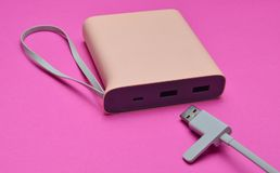 External battery for charging smartphones and gadgets with a usb cable close-up on a pink background. Power bank. stock photography