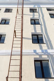 External Building Ladder in Sun. Orange colored metal ladder on the exterior of a white painted building with shadows from the sun. Nobody present in the image Royalty Free Stock Image