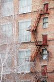 External fire escape staircase on an old brick building of factory, plant. Big windows, white birch trees grows near. External fire escape staircase on an old Royalty Free Stock Photography