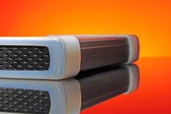 External Hard Disk. On orange background with reflexion Stock Photo