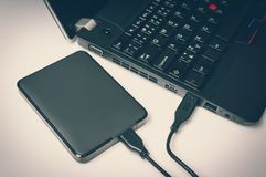 External hard disk HDD connected to laptop computer. By USB cable - retro style Stock Photo