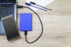 External hard drive connecting to laptop with smartphone, pens and paper on wooden desk. Business concept Royalty Free Stock Images