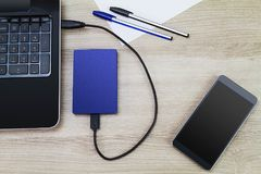 External hard drive connecting to laptop with smartphone, pens and paper on wooden desk. Business concept Stock Images