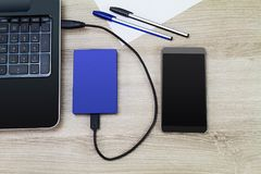 External hard drive connecting to laptop with smartphone, pens and paper on wooden desk. Business concept Stock Photography