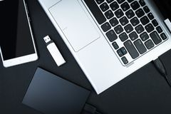 External hdd connected to the laptop, USB flash drive and smartphone on a black background. Top view. The concept of portable data storage Stock Photography