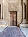 Bricks stone wall with arabesque decorated wooden door framed by stone ornate cylindrical columns, al Rifai Mosque, Cairo, Egypt Royalty Free Stock Image