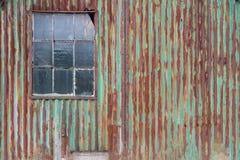 External rusty corrugated iron wall of a building. External rusty corrugated iron wall with weathered Stock Photo